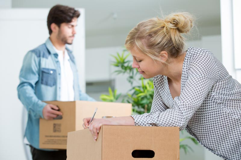 wife writing information on box for relocation